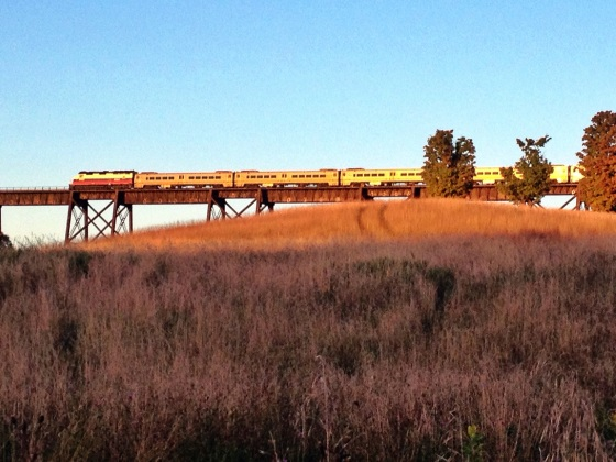 The train travels through Cornwall on the trestle. Sunset.
